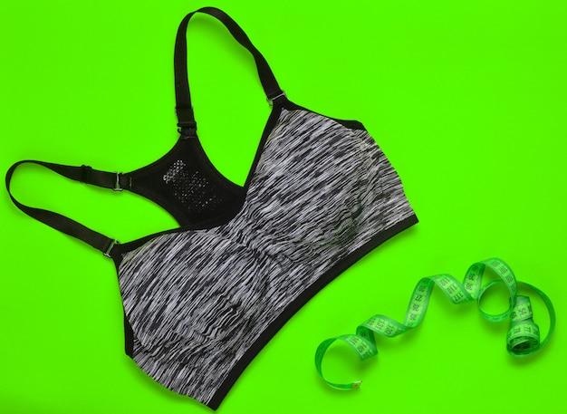 Sports top feminino e régua para medir as proporções do corpo em um verde.