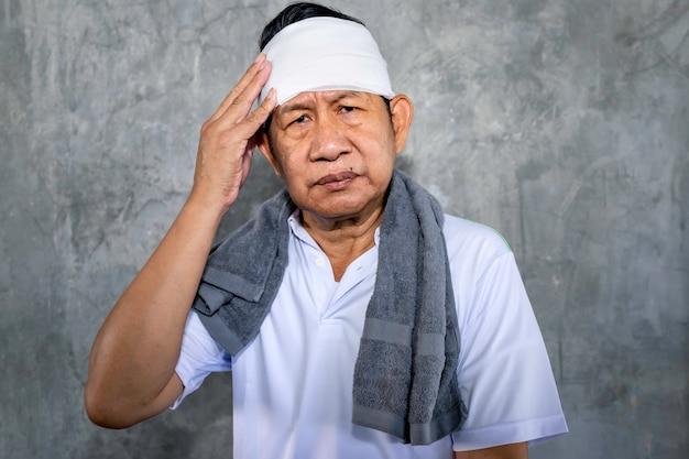 Sportswear asiático sênior do homem na dor com ferimento sério na cabeça.