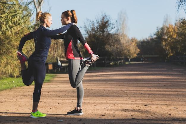 Sportswomen esticar as pernas no parque