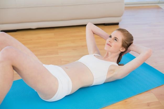 Sporty fit woman fazendo sit ups em fitness studio