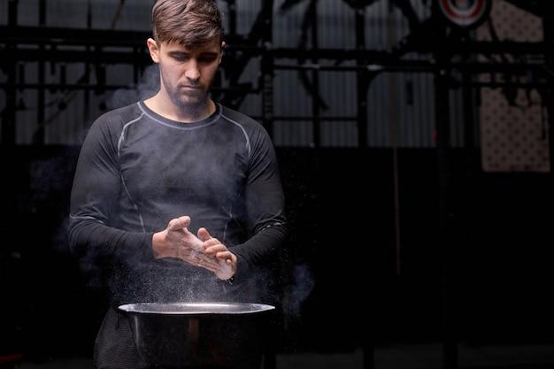 Spotsman se preparando para o treinamento de levantamento de peso, usando talco, preparando as mãos para o treino. na academia. conceito de esporte e musculação