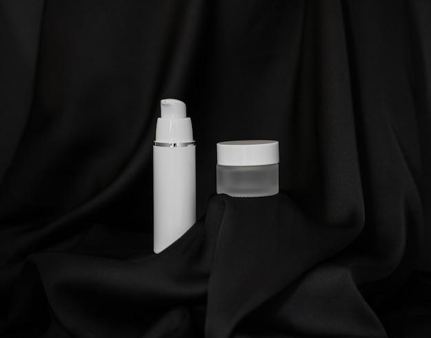 Spray cosmético e frasco cosmético ficam em fundo de seda preta