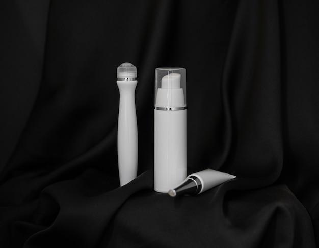 Spray cosmético, rolo cosmético e tubo cosmético em fundo de seda preta