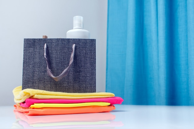 Spray de ambientador, amaciante em um saco de papel na pilha de roupa colorida limpa e passada a ferro. conceito de cuidados de têxteis e roupas.
