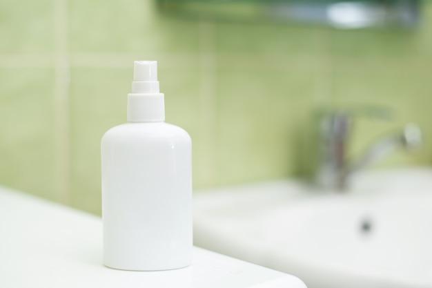 Spray de desinfetante para as mãos fica na máquina de lavar perto da pia no banheiro