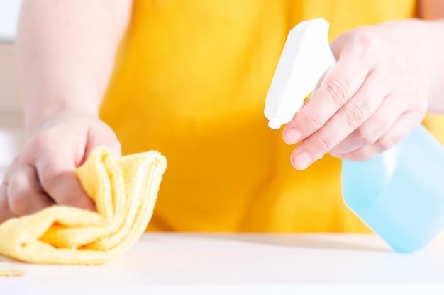 Spray de garrafa de cloro azul. mulher usando detergente e limpe. limpeza com spray de limpeza.