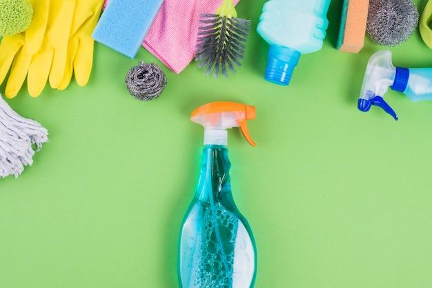 Spray de garrafas com líquido azul perto de vários equipamentos de limpeza