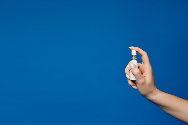 Spray higiênico para desinfecção em uma mão feminina pura com manicure isolado em um azul com espaço de cópia. desinfetante para as mãos na mão feminina arrumada. foto de anúncio de higiene