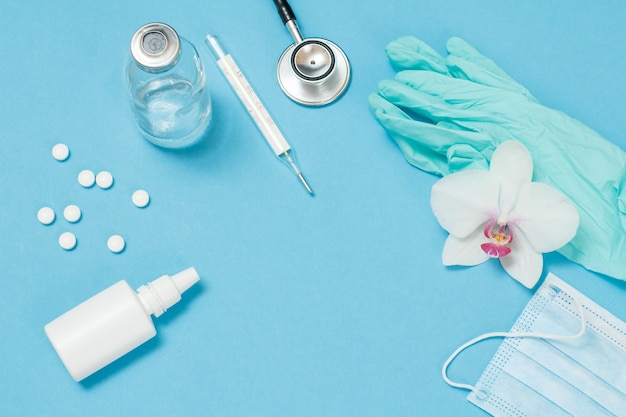 Spray nasal, comprimidos, termômetro de mercúrio de vidro, estetoscópio e luvas de látex, máscara médica para proteção pessoal. vista do topo. conceito de kit protetor de vírus.