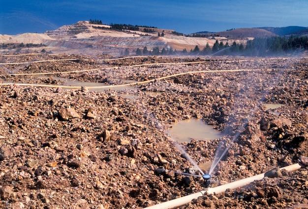 Sprinklers molhando terra escavada