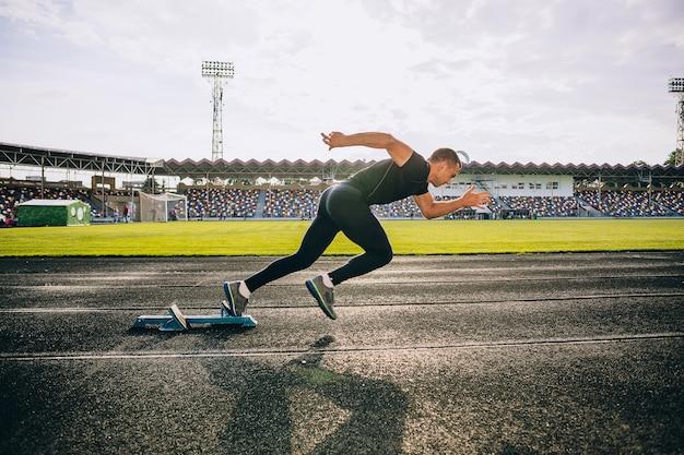 Sprinter deixando blocos de partida na pista de atletismo
