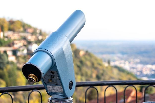 Spyglass olhando para as montanhas em como, itália. visor monocular operado por moedas.