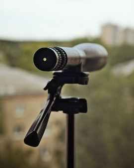 Spyglass ou telescópio em tripé ficam perto da janela. vigilância e conceito de espionagem.
