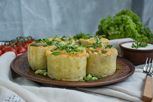 Squash recheado com carne picada, legumes e polvilhados com queijo duro. vista lateral.