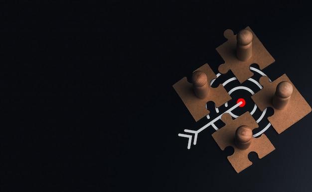 Stakeholder, conexão de negócios, trabalho em equipe e conceito de construção de equipes. figura de madeira de close-up, como empresário em quebra-cabeças com o símbolo do ícone de alvo em um fundo escuro com espaço de cópia.