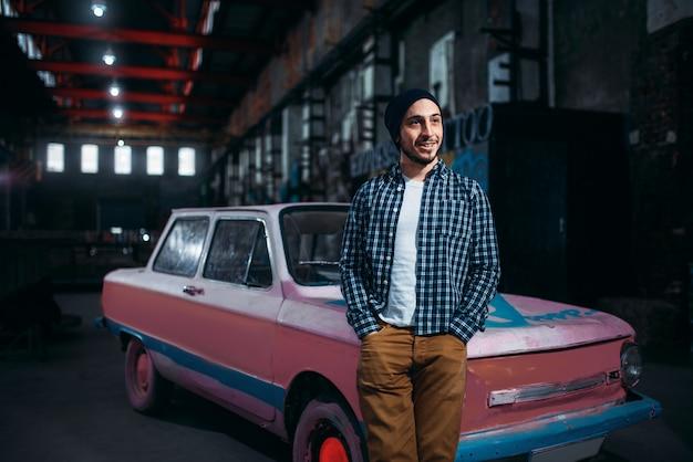 Stalker, viajante sozinho posa contra carro retrô da urss, interior de fábrica antiga.