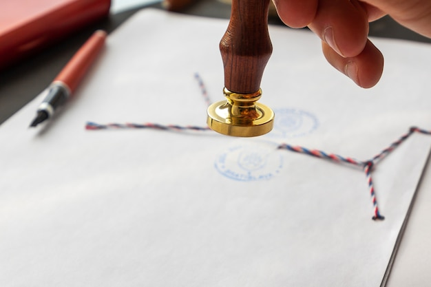 Stamper da cera do notário. envelope branco com selo de cera marrom, carimbo de ouro. maquete de design responsivo, plana leigos. natureza morta com acessórios postais.