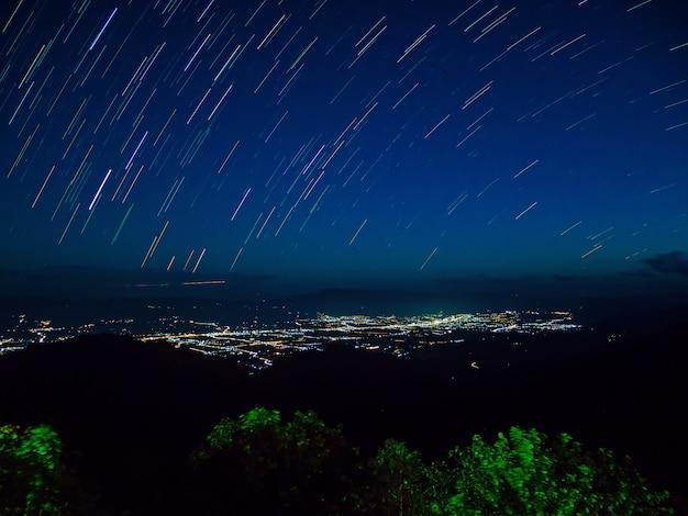 Star trail com montanhas rever e fotografia de paisagem de luzes de cidades
