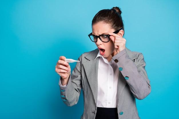 Stare estupor freelancer verificar termômetro eletrônico de alta temperatura covid sintoma isolado fundo de cor azul