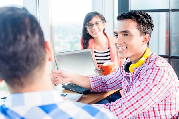 Start-ups criativos asiáticos discutindo novo projeto no escritório