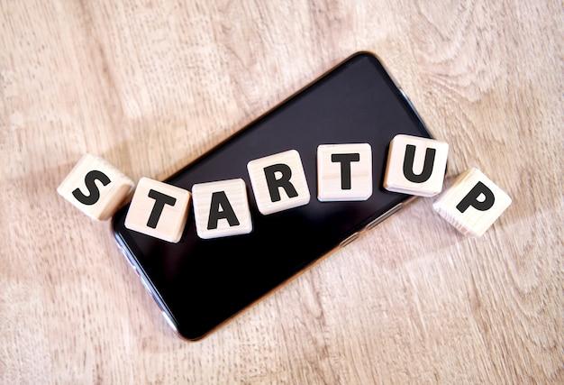 Startup de texto em cubos de madeira em um smartphone preto. cubos colocaram em um smartphone preto na mesa de madeira.