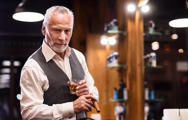 Status elevado. retrato de homem barbudo sênior bonito elegante em pé com copo de uísque e charuto na barbearia.