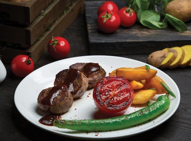 Steakes de carne redonda em molho teriyaki com pimenta e batatas.