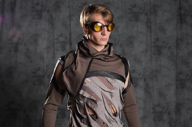 Steampunk ou personagem de estilo pós-apocalíptico, um jovem em um terno grunge. uma jaqueta com mangas fechadas com fendas e óculos de proteção na cabeça, uma roupa grunge