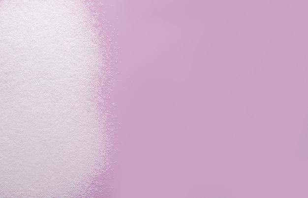 Stevia adoçante em pó derramado sobre um fundo rosa. copie o espaço