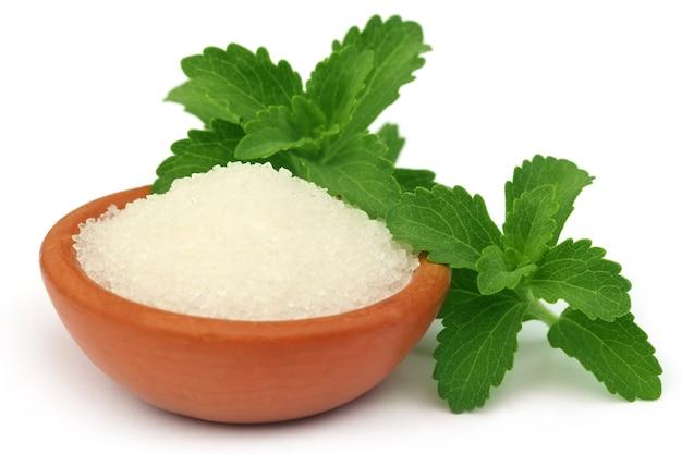 Stevia com açúcar em uma tigela marrom sobre fundo branco