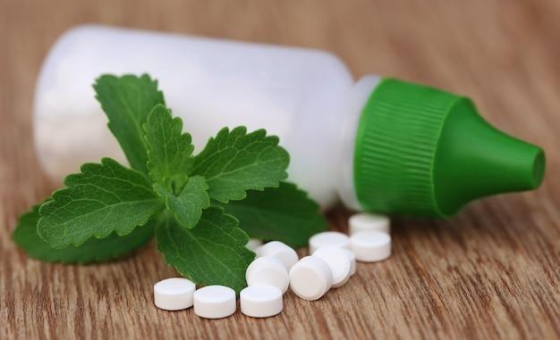 Stevia com comprimidos adoçantes e garrafa na superfície de madeira