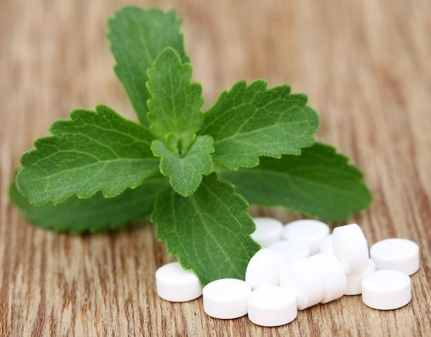 Stevia com comprimidos na superfície de madeira