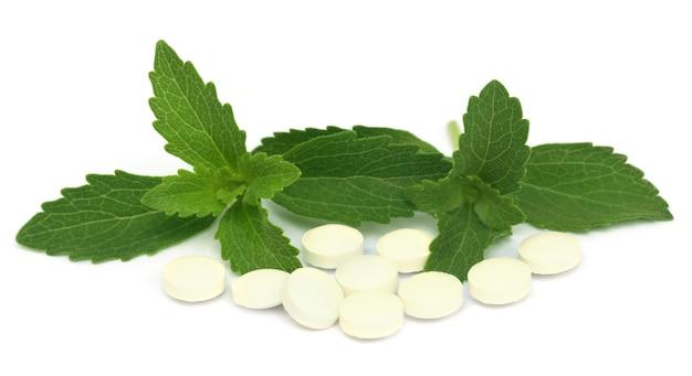 Stevia com comprimidos sobre fundo branco