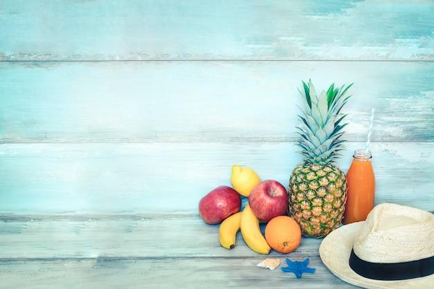 Stillife de conceito de verão. uma pilha de frutas frescas, chapéu de palha e uma garrafa de suco multivitamínico na frente de uma madeira rústica azul.