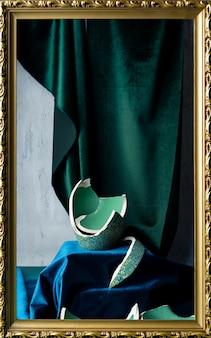 Stilllife com restos de vaso de cor verde-azulado quebrado, veludo verde esmeralda e azul escuro e moldura