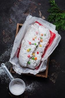 Stollen de grão integral com passas e açúcar de confeiteiro em um guardanapo de linho com peneira, fita vermelha sobre a velha mesa de concreto escuro. bolo de natal alemão tradicional.