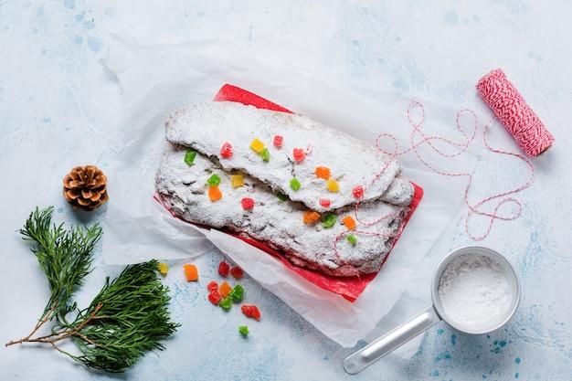 Stollen de grão integral com passas e açúcar de confeiteiro em um guardanapo de linho com uma peneira, fita vermelha sobre o fundo de concreto nevado azul claro. bolo de natal alemão tradicional. vista do topo.