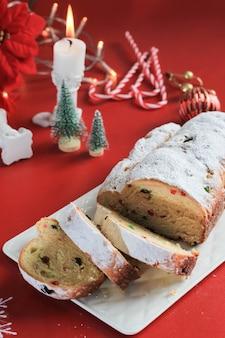 Stollen de natal em fundo rústico. sobremesa de pastelaria festiva de natal tradicional do alemão. stollen para o natal, red concept
