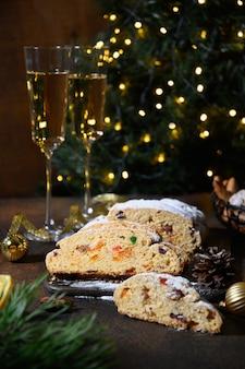 Stollen tradicional decorado com corda festiva em uma mesa escura festiva com árvore de natal