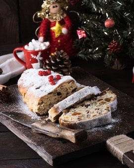 Stollen, um bolo europeu tradicional com nozes e frutas cristalizadas, é polvilhado com açúcar de confeiteiro e cortado em pedaços em uma placa de madeira marrom