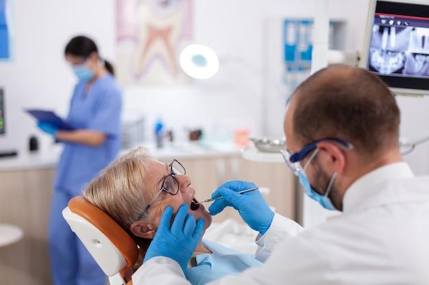 Stomatolog usando máscara facial durante a consulta com uma mulher sênior usando espelho em ângulo