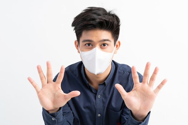 Stop civid-19, homem asiático usando máscara facial mostra gesto com as mãos para parar surto do vírus corona