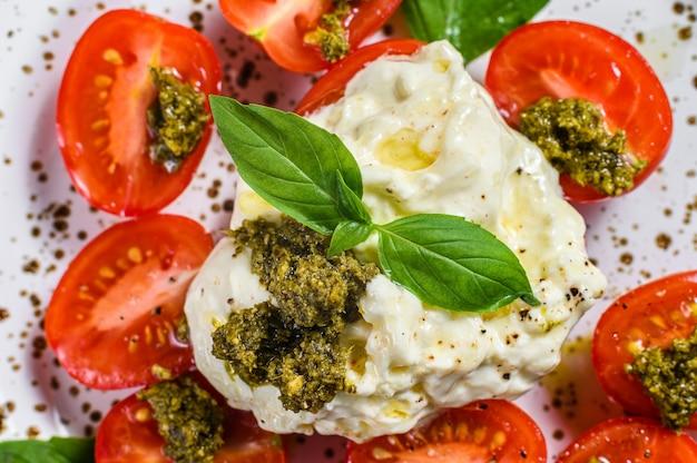 Stracciatella (mussarela de búfala) em um pequeno prato servido com manjericão e tomate fresco.
