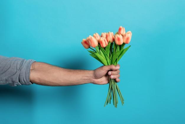Straigth de mão do homem com um buquê de tulipas