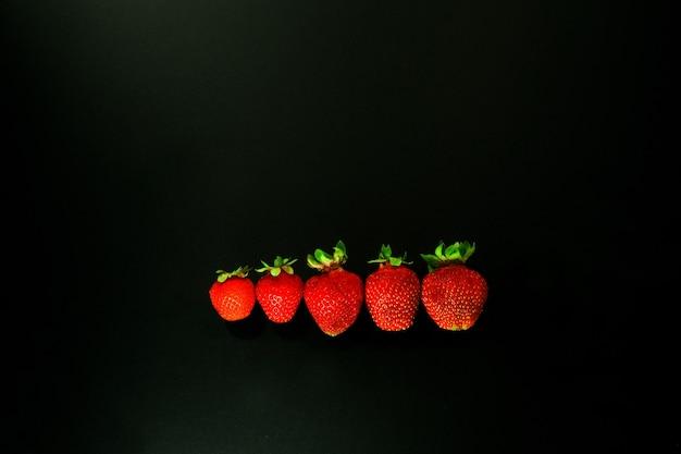 Strawbery vermelho sobre fundo preto. palha vermelha em linha