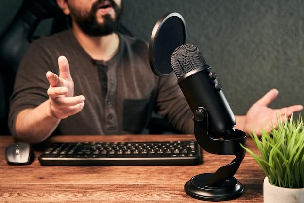 Streamer de jovem falando ao microfone em um estúdio caseiro
