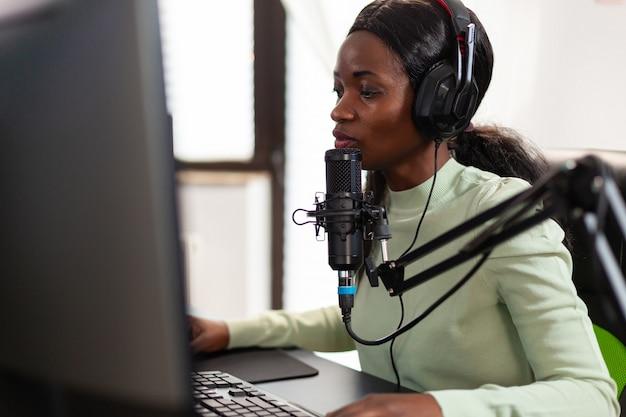Streamer esport competitivo falando ao microfone com colegas de equipe durante a competição ao vivo streaming de videogames virais para se divertir usando fones de ouvido e teclado para campeonatos online.