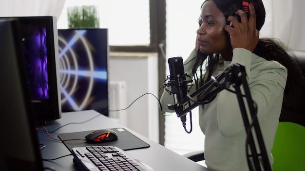 Streamer preto profissional sentado em uma cadeira de jogo colocando um fone de ouvido falando com jogadores usando um microfone profissional jogando videogame de atirador espacial durante um torneio online, falando no chat de streaming