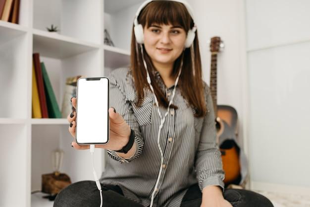 Streaming de blogueira feminina com smartphone e fones de ouvido