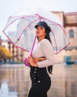 Street style de uma jovem morena latina na chuva da cidade com um guarda-chuva transparente